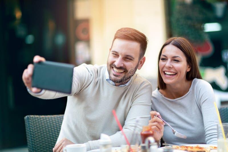 Acople usando tabuletas digitais ao sentar-se no restaurante foto de stock royalty free