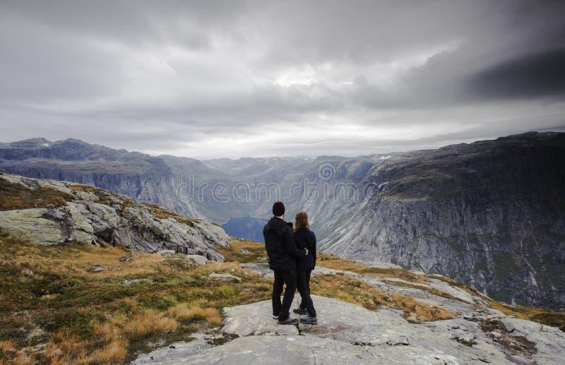Acople a viagem, os pares de A olhando a grande vista de montanhas e de geleiras da neve em Noruega imagens de stock royalty free