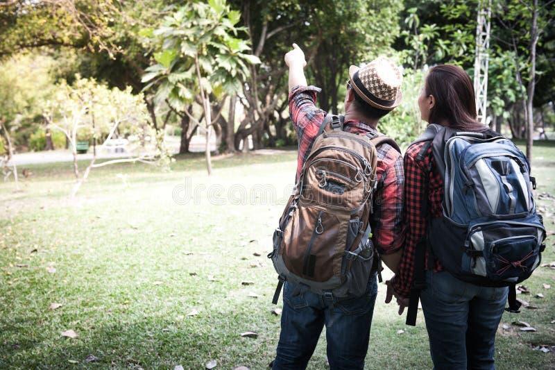 Acople viajantes com as trouxas que relaxam na selva dos verdes Trave imagens de stock