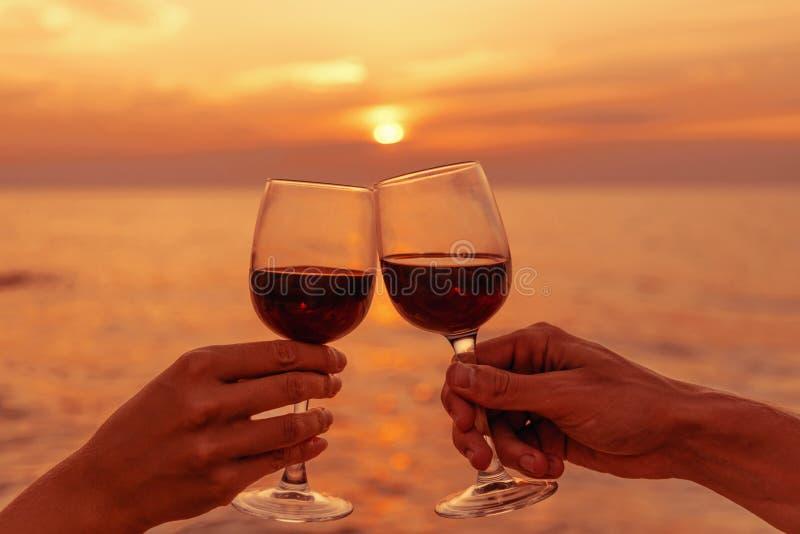 Acople vidros de vinho do tinido no por do sol do mar imagem de stock royalty free