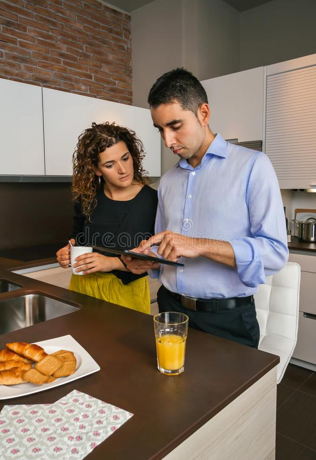 Acople a vista da tabuleta eletrônica no café da manhã na casa foto de stock royalty free