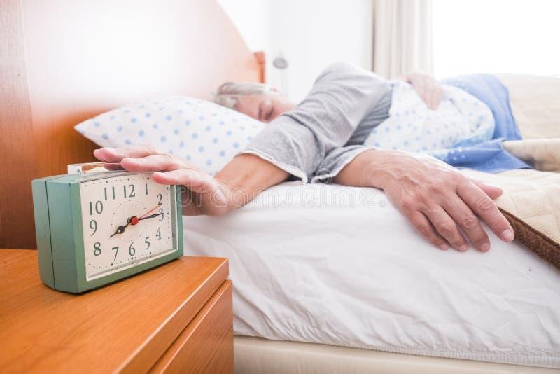 Acordando a cena diária do alarme da parada para a mulher adulta caucasiano na manhã em casa não queira ir escritório mas aposent fotos de stock