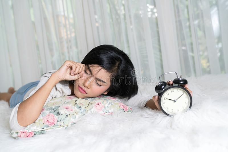 Acordar feliz da mulher e o despertador que tem um bom dia foto de stock