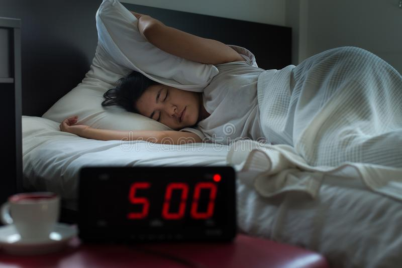 Acordar forçado de obtenção fêmea asiático novo cedo na manhã no pulso de disparo do ` de 5 o, despertador fotografia de stock royalty free