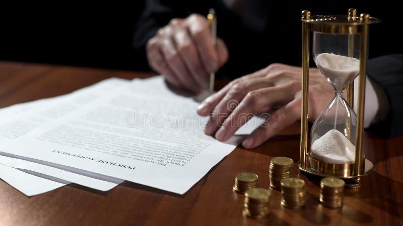 Acordo de compra de assinatura masculino do comprador ou do vendedor, dinheiro e ampulheta na tabela fotos de stock royalty free