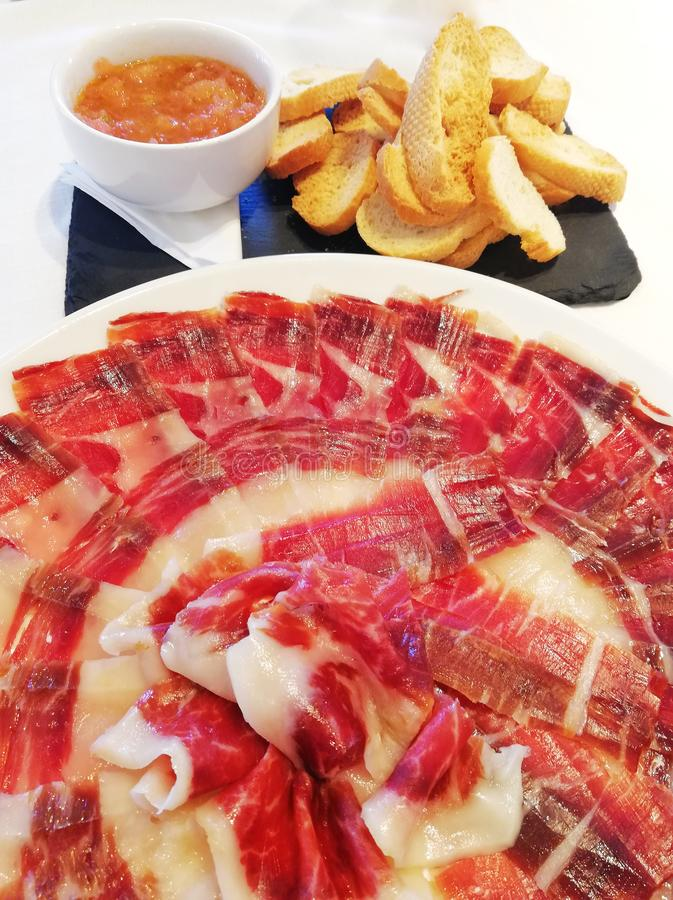 100 Acorn-fed iberico ham. Pata negra. Acorn-fed Iberico Ham. pata negra, ham dish with the fat veining detail next to a cup of crushed tomato and some toasted stock photography