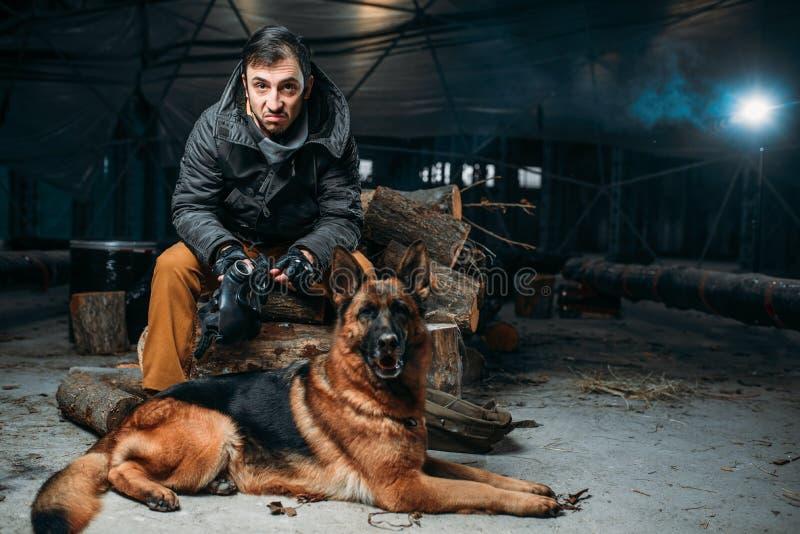 Acosador y perro, amigos en mundo apocalíptico de los posts imagenes de archivo