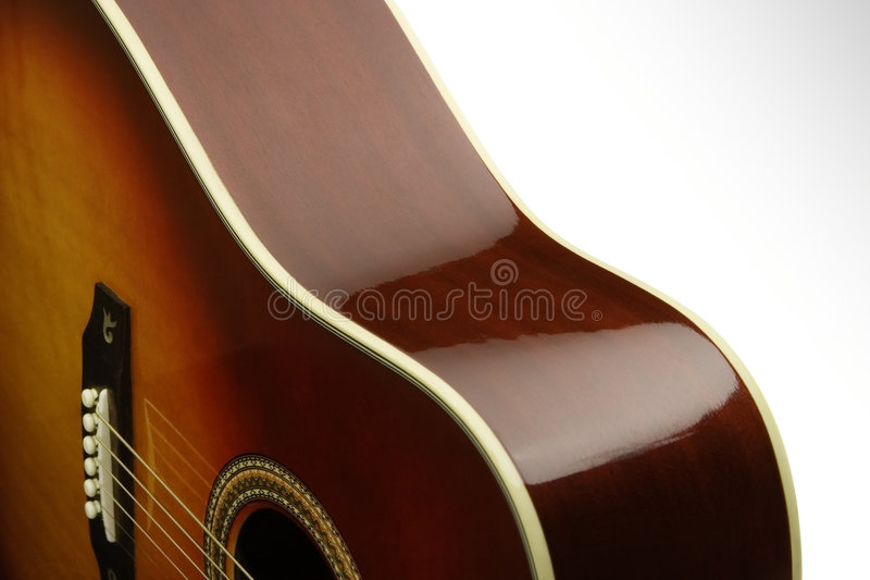 Acoustic Curves. Close-up of the smooth curves of an acoustic guitar on a white background royalty free stock photography