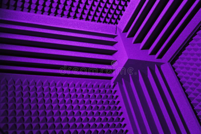 Acoustic foam absorber and bass traps for sound dampering, purple background stock photography