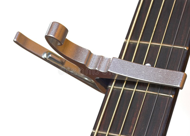 Acoustic Guitar with Capo. Detail of the neck of an acoustic guitar with a capo fitted. White Background stock photography