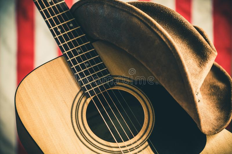 Acoustic Guitar and Cowboy Hat with American Flag. Music guitar close-up country and western music closeup acoustic guitar american flag royalty free stock photos