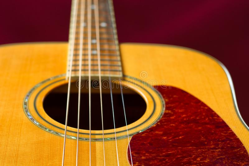 Acoustic Guitar Detail. Rich color solid Spruce top acoustic guitar detail. Selective focus on strings royalty free stock images