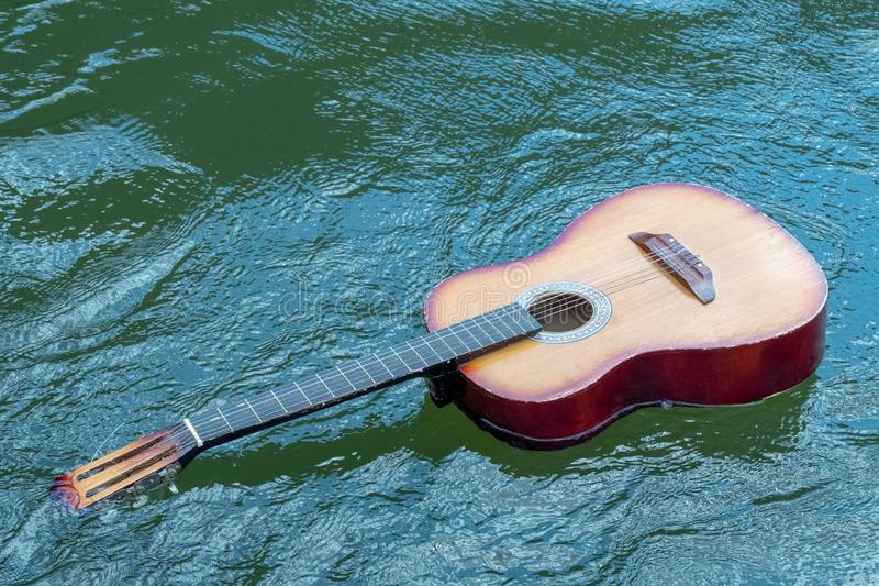 Acoustic guitar floats in the water. The concept of shipwreck, flood, tragedy of musicians in nature. Copy space. Acoustic guitar floats in the water. The stock photo