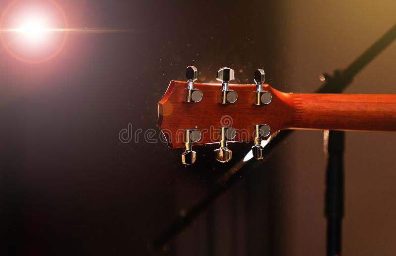 Acoustic guitar head with tuning pegs, neck, frets and fingerboard, back view. Headstock of the guitar over concert stage. Background with light flare effect royalty free stock images