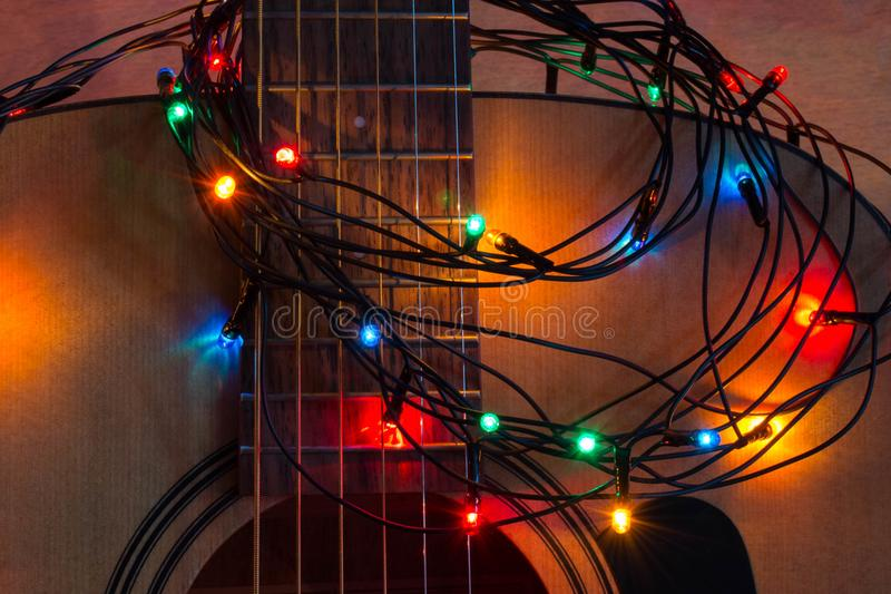 Acoustic guitar with lighted garland royalty free stock photography