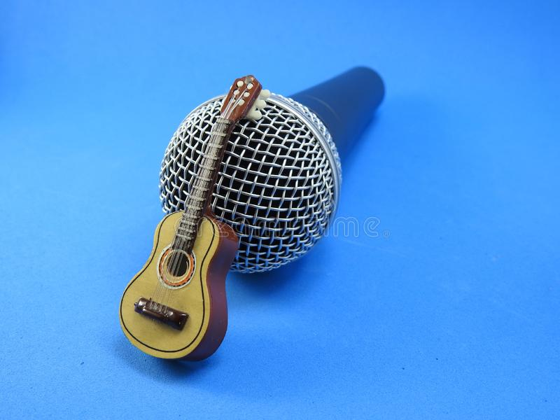 An acoustic guitar miniature propped up on a dynamic microphone stock photo
