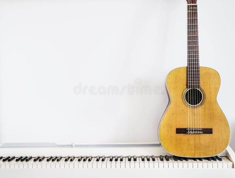 Acoustic guitar on piano keyboard in front of white wall royalty free stock image