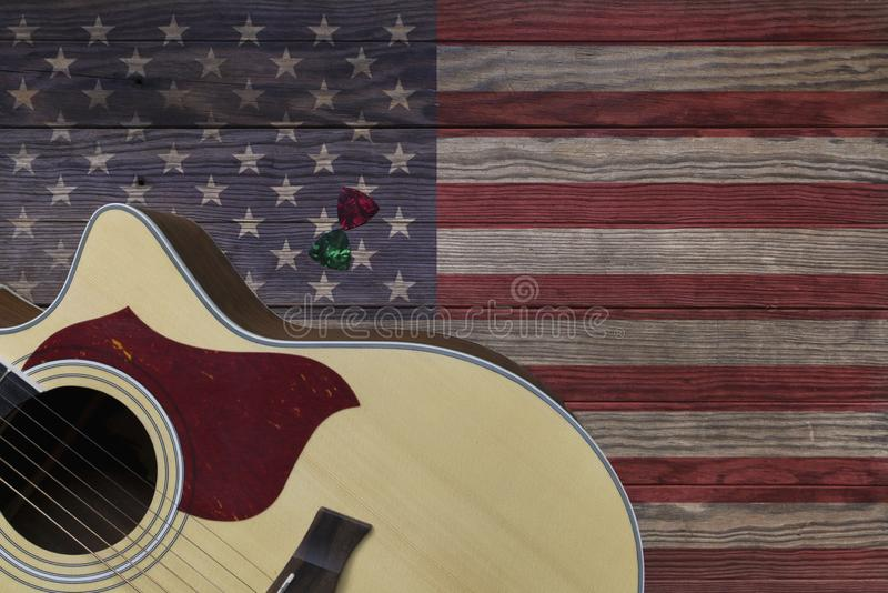 Acoustic guitar placed on an old wooden table, With a picture of an American flag on wood royalty free stock photo