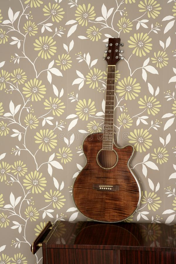 Acoustic guitar retro on vintage 60s wallpaper. Wooden furniture royalty free stock photography