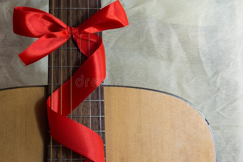Acoustic guitar with a ribbon bow royalty free stock photos