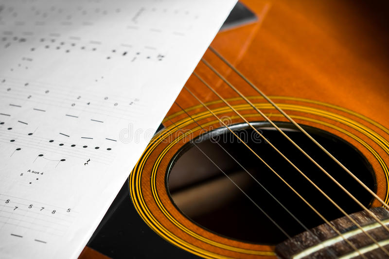 Acoustic guitar with song note. Paper royalty free stock photography