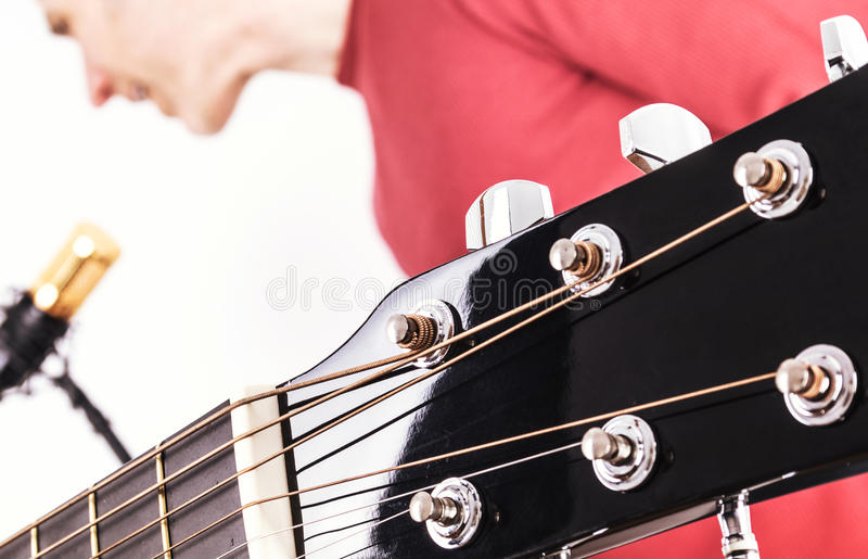 Acoustic Guitar Tuners with Singer in Background. Closeup view showing the string tuners of an acoustic guitar with a male vocalist singing into a gold and black royalty free stock image