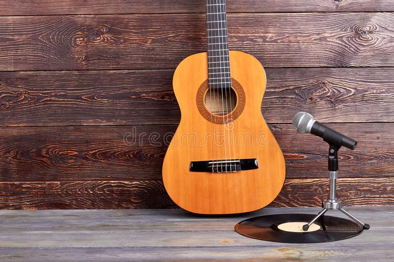 Acoustic guitar, vinyl record and microphone. Musical instruments on wooden background and copy space stock images