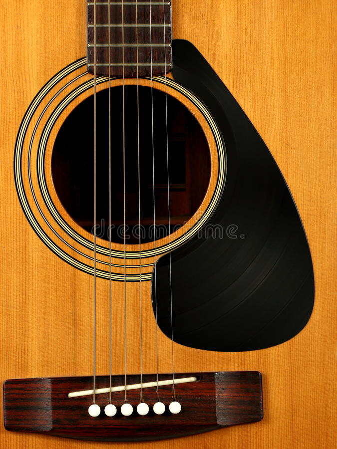 Acoustic Guitar with Vinyl Record for a Pick Guard. An acoustic guitar is shown with a pick guard made from a vinyl record stock photography