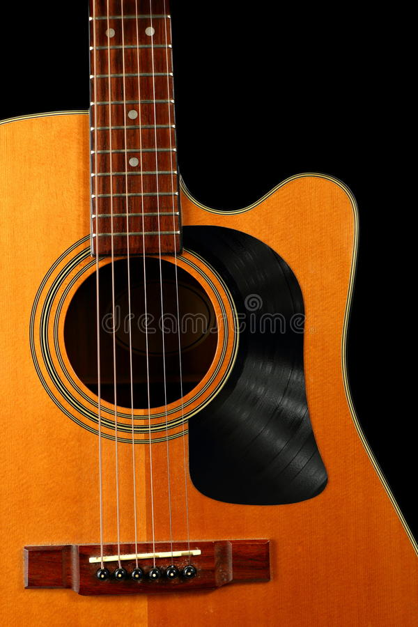Acoustic Guitar with Vinyl Record for a Pick Guard. An acoustic guitar is shown with a pick guard made from a vinyl record stock images