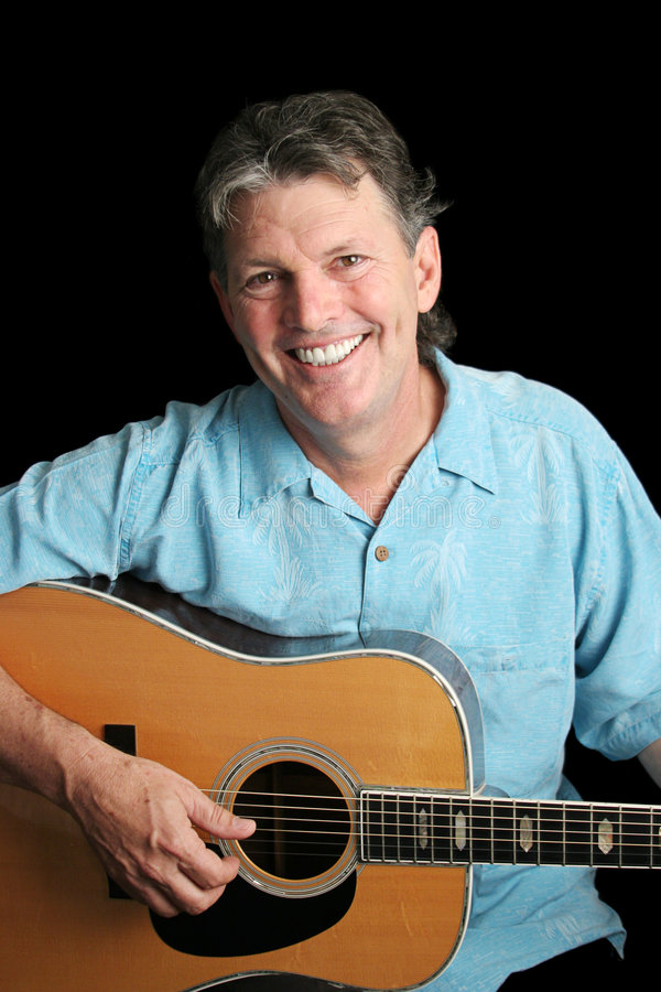 Acoustic Jamming. A handsome, smiling guitarist jamming on his acoustic guitar stock photography
