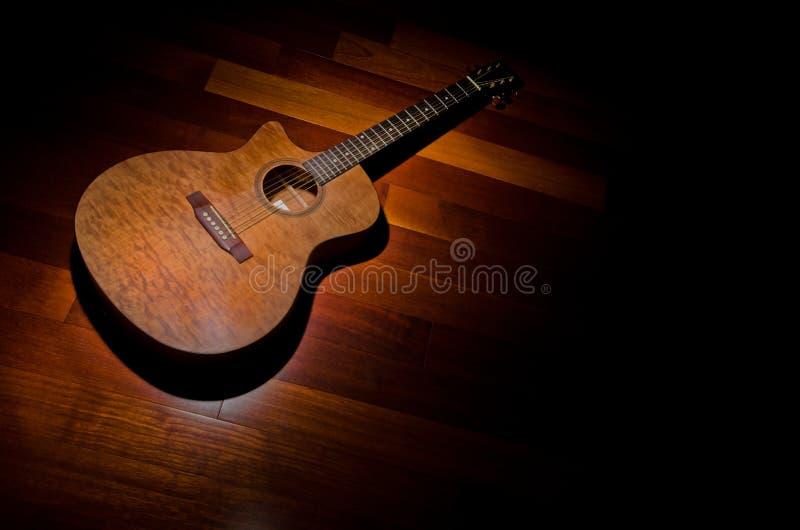 Acoustic mahogony guitar under a spotlight stock image
