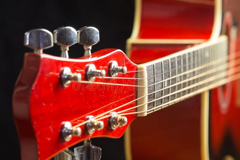 Acoustic red guitar resting in the background with a copy of the hand space, playing acoustic guitar, close-up on the royalty free stock images