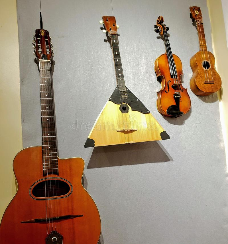 Acoustic string musical instruments displayed on a wall. Acoustic string musical instruments  on a wall, school, song, ensemble, group, strings stock photos