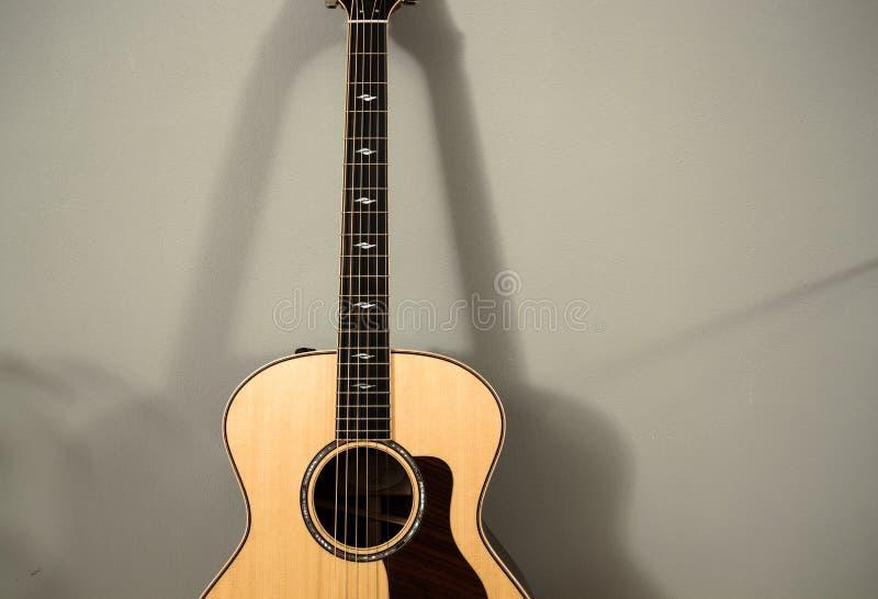 Acoustig gitarr som ligger på den gråa väggen arkivfoto