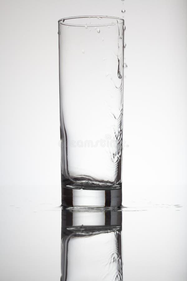 Acqua in bianco e nero del bicchiere vuoto bagnato nel concetto di moto immagine stock