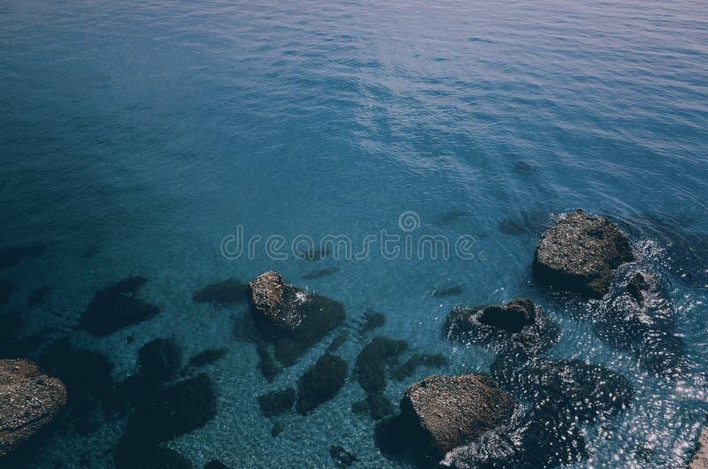 Acqua blu dell'oceano con le pietre fotografie stock