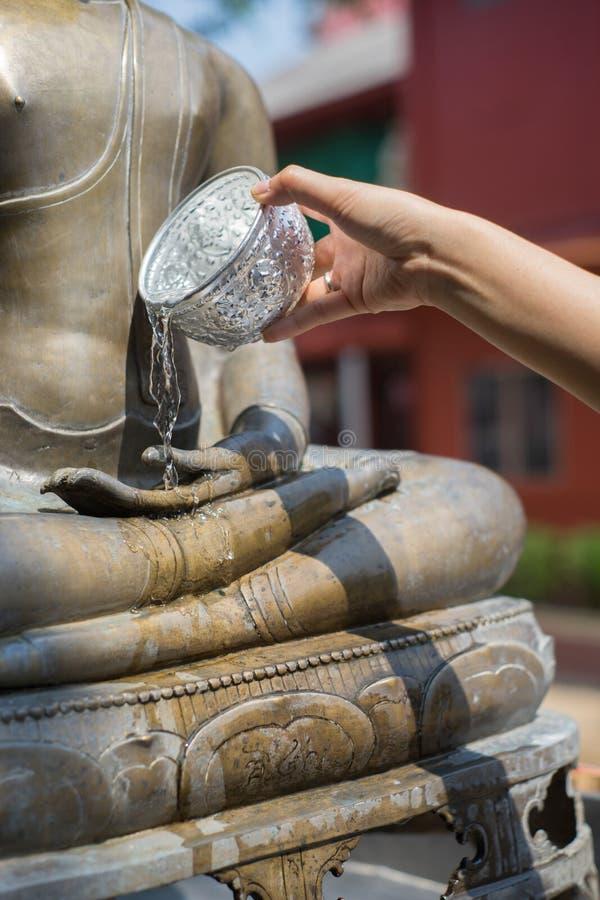 Acqua che versa alla statua del Buddha immagini stock libere da diritti