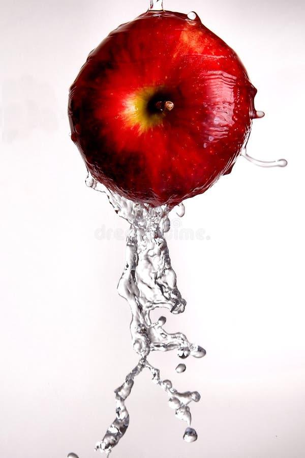 Acqua che versa fuori dalla mela rossa. immagini stock libere da diritti