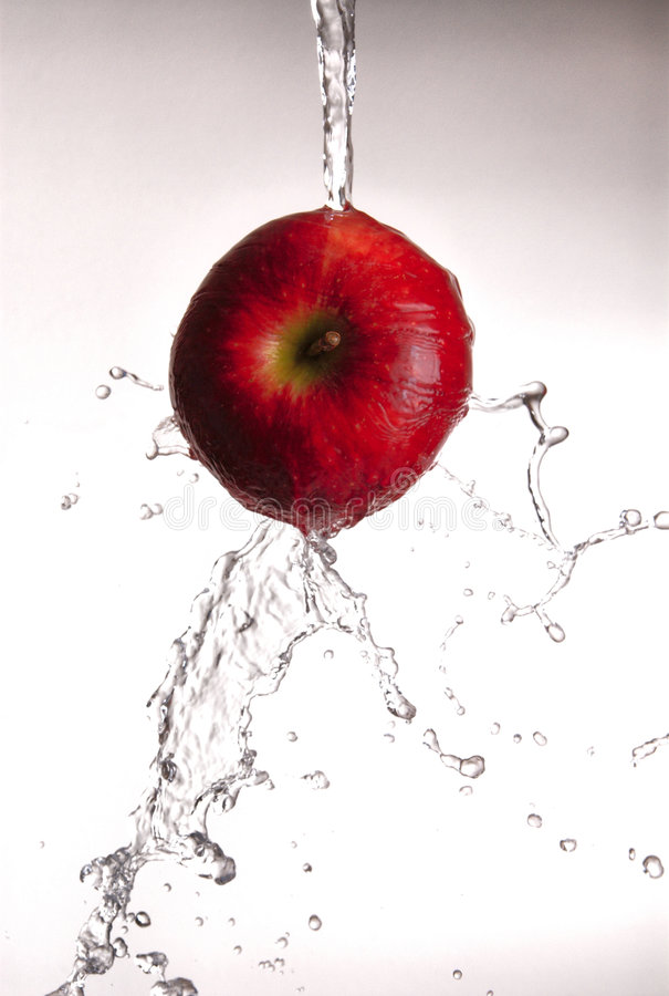 Acqua che versa fuori dalla mela rossa. immagine stock