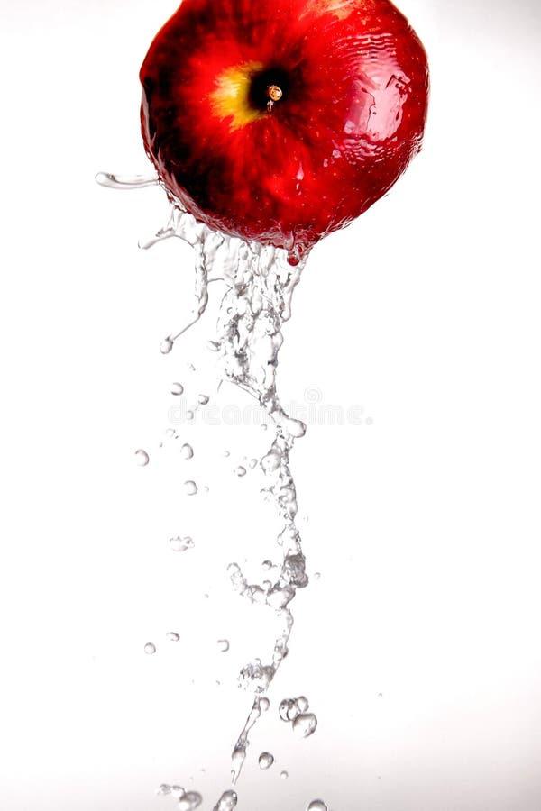 Acqua che versa fuori dalla mela rossa. fotografia stock libera da diritti