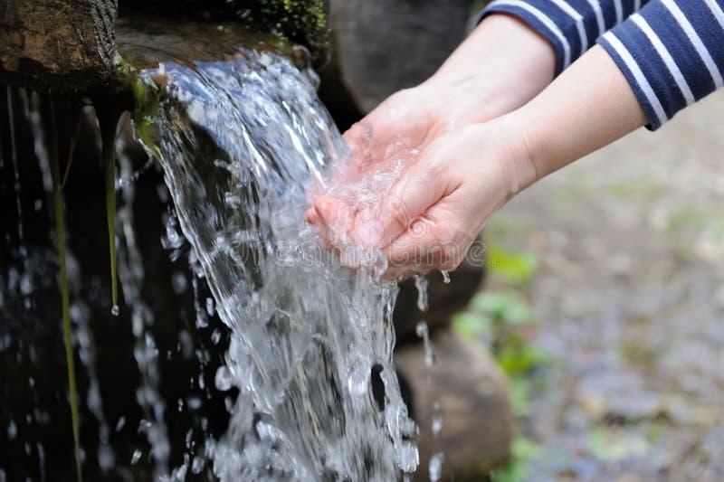 Acqua che versa in mano della donna immagini stock