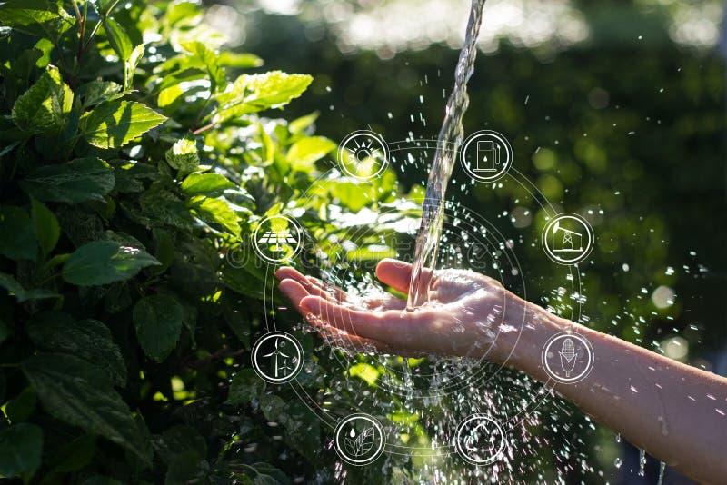 Acqua che versa in mano della donna con le fonti di energia per rinnovabile, sviluppo sostenibile delle icone ecologia immagine stock libera da diritti