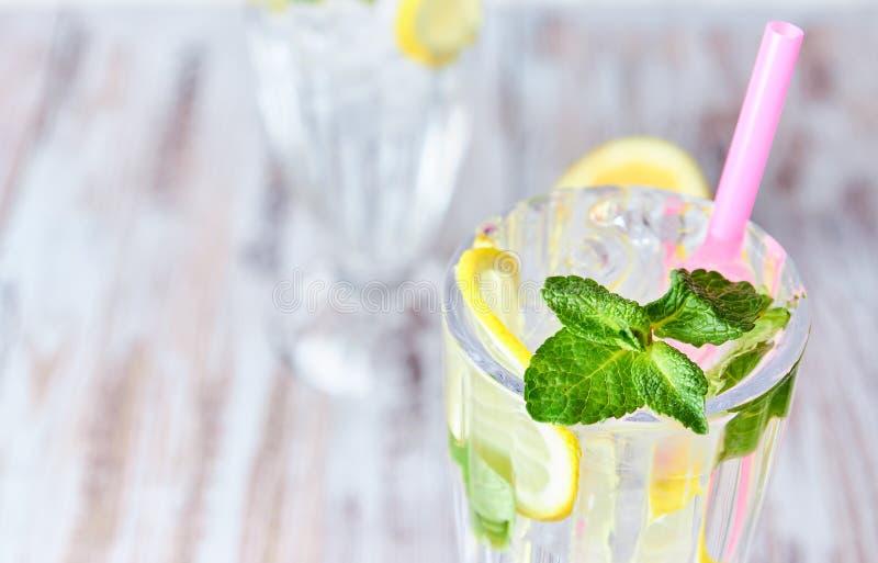Acqua con ghiaccio, le fette del limone e la menta in un vetro con paglia su un fondo di legno leggero Copi lo spazio estate, bev fotografia stock libera da diritti