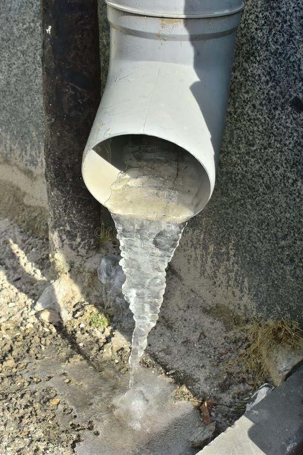 Acqua congelata primo piano in grondaia grigia della casa in tempo di inverno sulla via della città fotografie stock