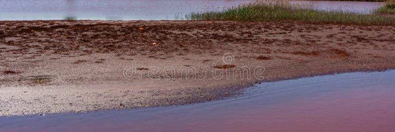 Acqua contaminata e suolo con gli ossidi di ferro nella zona industriale Insegna per progettazione fotografie stock