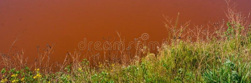 Acqua contaminata e suolo con gli ossidi di ferro nella zona industriale Insegna per progettazione fotografia stock libera da diritti
