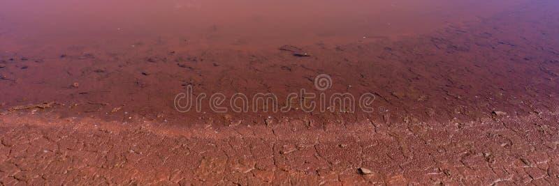 Acqua contaminata e suolo con gli ossidi di ferro nella zona industriale Insegna per progettazione immagini stock