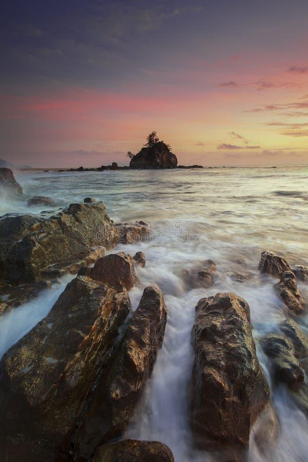 Acqua corrente sulle rocce di Brown durante il tramonto giallo fotografia stock