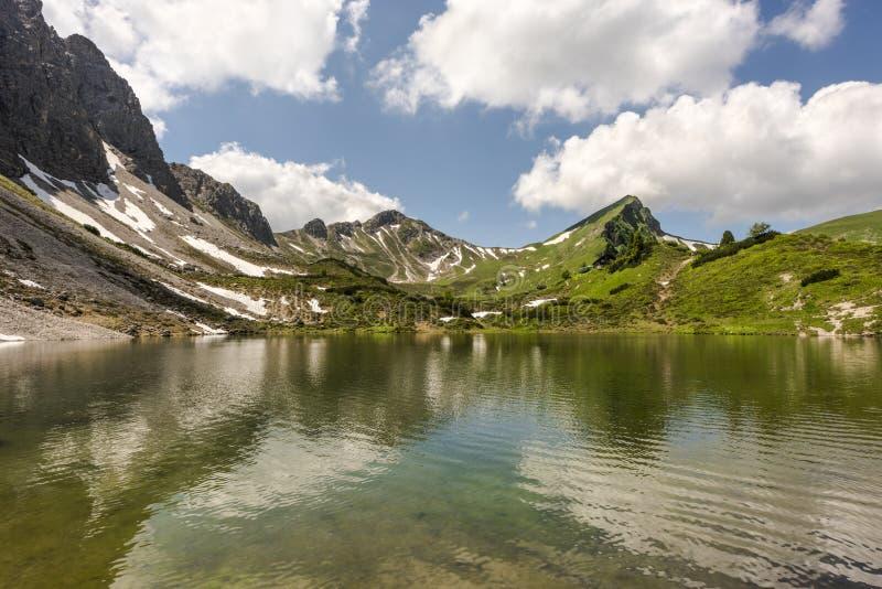 Acqua cristallina del lago alpino Lache in alta valle di Tannheimer con la capanna di Landsberger del rifugio della montagna, Tir fotografia stock libera da diritti