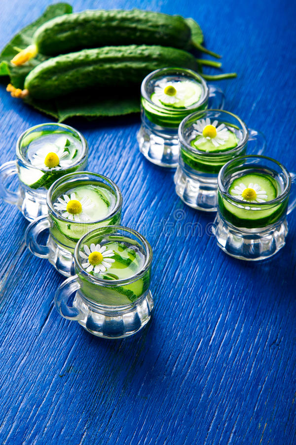 Acqua del cetriolo in sei barattoli di vetro del piccolo muratore su fondo blu rustic detox immagini stock libere da diritti